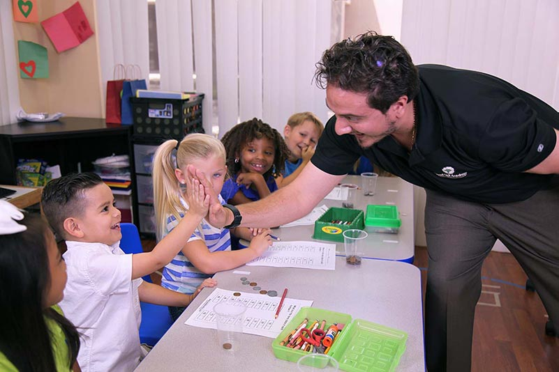 Smiling student getting a high five from his ABA teacher during Club TLC