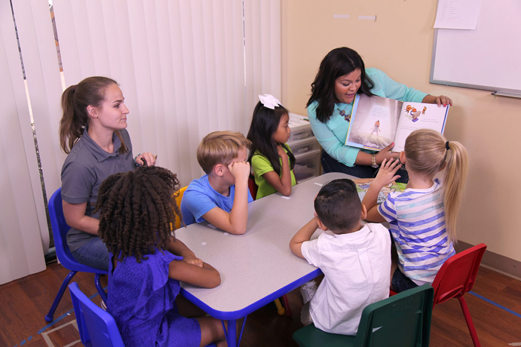 Group of students listening to their teacher read a story